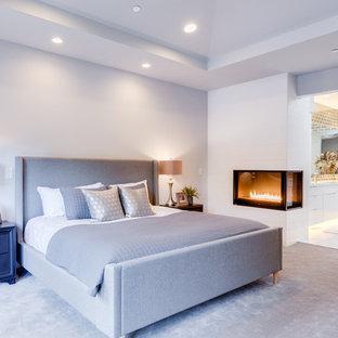 Idéer för ett mellanstort modernt huvudsovrum, med vita väggar, heltäckningsmatta, en öppen hörnspis, en spiselkrans i trä och grått golv
