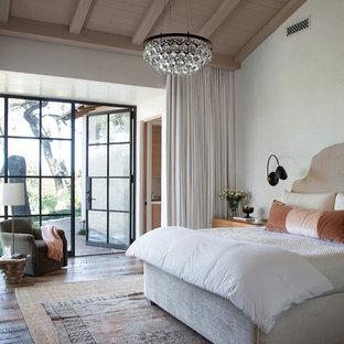 Mediterranes Schlafzimmer mit weißer Wandfarbe und dunklem Holzboden in Austin