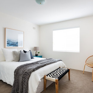 This is an example of a beach style guest bedroom in Sydney with white walls, carpet and brown floor.