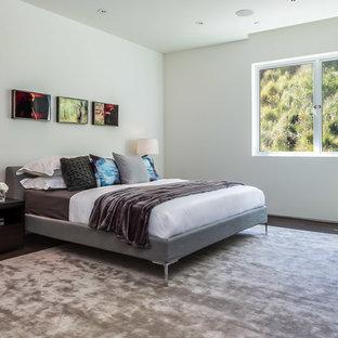Exemple d'une chambre d'amis moderne de taille moyenne avec un mur blanc et un sol en bois foncé.