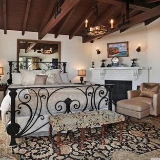 Imagen de dormitorio tipo loft, rústico, grande, con paredes blancas, suelo de madera clara, chimenea de esquina y marco de chimenea de ladrillo