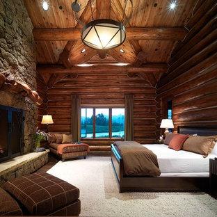 Modelo de dormitorio principal, rural, de tamaño medio, con chimenea tradicional, paredes marrones, suelo de madera oscura, marco de chimenea de piedra y suelo marrón
