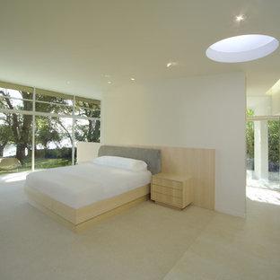Foto di una grande camera matrimoniale minimalista con pareti beige, pavimento in pietra calcarea e nessun camino