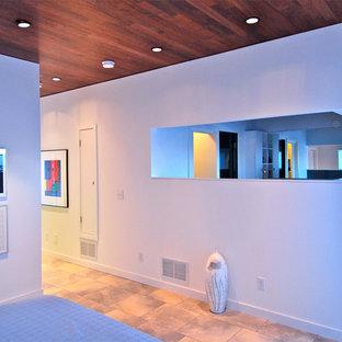 Modelo de dormitorio tipo loft, minimalista, de tamaño medio, con paredes blancas, suelo de baldosas de porcelana y suelo gris