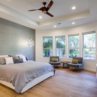 Großes Modernes Hauptschlafzimmer ohne Kamin mit weißer Wandfarbe und hellem Holzboden in Dallas