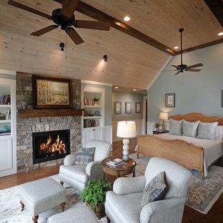 Aménagement d'une chambre montagne avec un mur bleu, un sol en bois foncé, une cheminée standard, un manteau de cheminée en pierre de parement, un sol marron, un plafond voûté, un plafond en bois et boiseries.