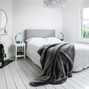 Scandinavian bedroom in Other with grey walls, painted wood flooring and white floors.