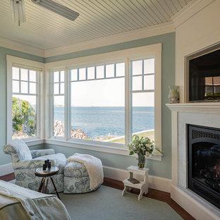 Idee per una camera matrimoniale costiera di medie dimensioni con pareti verdi, pavimento in legno massello medio, camino ad angolo e cornice del camino in pietra