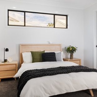 Contemporary bedroom in Brisbane with white walls, carpet and grey floor.