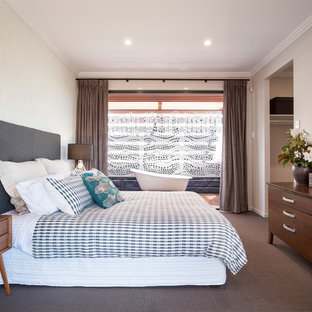 Inspiration for a contemporary carpeted bedroom remodel in Brisbane with beige walls