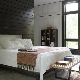 Ejemplo de dormitorio principal, exótico, de tamaño medio, sin chimenea, con suelo de cemento, paredes blancas y suelo gris
