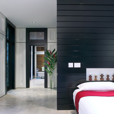 Example of a mid-sized trendy master concrete floor and gray floor bedroom design in Miami with white walls and no fireplace