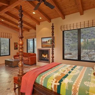 Modelo de habitación de invitados de estilo americano, grande, con paredes beige, chimenea tradicional, suelo de baldosas de porcelana y marco de chimenea de baldosas y/o azulejos