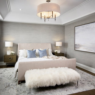 Design ideas for a large transitional master bedroom in Toronto with white walls, light hardwood floors, brown floor, coffered and wallpaper.