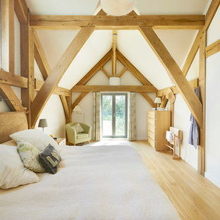 Inspiration for a rustic bedroom in West Midlands with white walls, light hardwood flooring and beige floors.