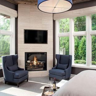 На фото: хозяйская спальня в стиле современная классика с серыми стенами, ковровым покрытием, угловым камином и фасадом камина из плитки с