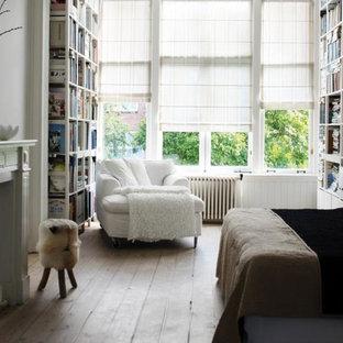 Foto de dormitorio tradicional renovado, de tamaño medio, con paredes blancas, suelo de madera clara, chimenea tradicional y marco de chimenea de hormigón