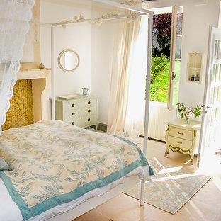 Ejemplo de habitación de invitados de estilo de casa de campo, de tamaño medio, con paredes blancas, suelo de travertino, chimenea tradicional, marco de chimenea de piedra y suelo beige
