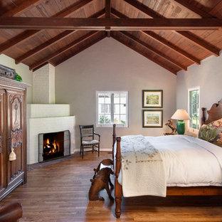 Modelo de dormitorio tradicional con paredes blancas, suelo de madera oscura, chimenea de esquina y marco de chimenea de ladrillo