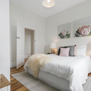 Bedroom - contemporary medium tone wood floor bedroom idea in Hobart with white walls