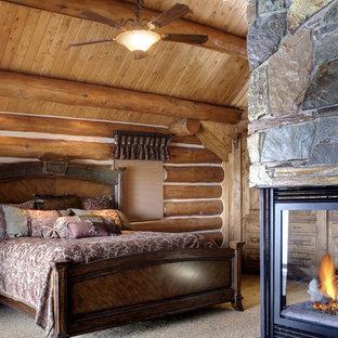 Idee per una camera matrimoniale rustica di medie dimensioni con moquette, camino bifacciale, cornice del camino in pietra, pareti marroni e pavimento beige
