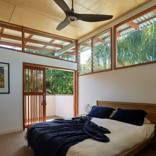 This is an example of a mid-sized tropical master bedroom in Brisbane with white walls, carpet and beige floor.