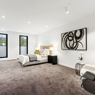 Large contemporary master bedroom in Melbourne with white walls, carpet, grey floor and no fireplace.