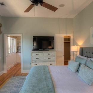 Modelo de dormitorio principal, costero, de tamaño medio, con paredes verdes y suelo de madera en tonos medios