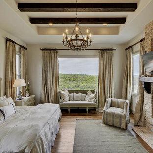 Imagen de dormitorio mediterráneo con paredes beige, suelo de madera en tonos medios, chimenea tradicional y marco de chimenea de ladrillo