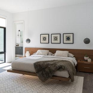 Modernes Hauptschlafzimmer mit weißer Wandfarbe und braunem Holzboden in Dallas