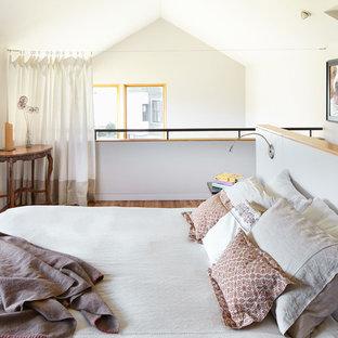 Imagen de dormitorio tipo loft, actual, pequeño, con paredes grises y suelo de madera clara