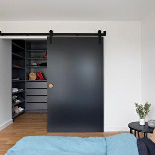 Cette photo montre une chambre parentale tendance de taille moyenne avec un mur blanc et un sol en bambou.
