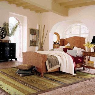 На фото: большая хозяйская спальня в средиземноморском стиле с белыми стенами и кирпичным полом без камина с