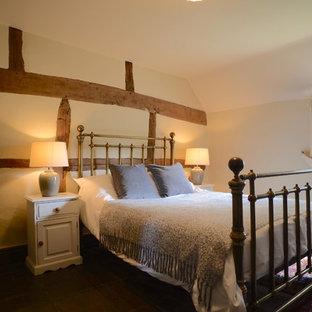 Imagen de habitación de invitados de estilo de casa de campo, de tamaño medio, con paredes blancas, suelo de madera oscura, chimenea de esquina, marco de chimenea de yeso y suelo marrón