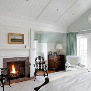 Foto de habitación de invitados tradicional, de tamaño medio, con paredes azules, suelo de madera en tonos medios, chimenea tradicional y marco de chimenea de ladrillo