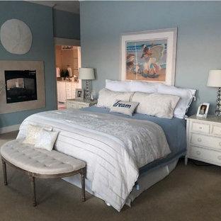 Ejemplo de dormitorio principal, tradicional renovado, grande, con paredes azules, moqueta, chimenea de doble cara, marco de chimenea de piedra y suelo beige