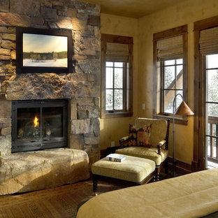 Modelo de dormitorio rural con marco de chimenea de piedra