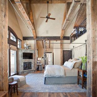 Exemple d'une grand chambre parentale montagne avec un mur beige, un sol en bois brun, une cheminée d'angle et un manteau de cheminée en pierre.