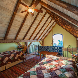 This is an example of a mid-sized country loft-style bedroom in Other with green walls, dark hardwood floors and no fireplace.
