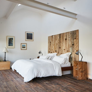 Photo of a large rustic master bedroom in Other with white walls, dark hardwood flooring, no fireplace and brown floors.