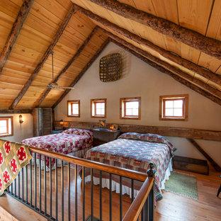 Ejemplo de dormitorio tipo loft, rural, con paredes blancas y suelo de madera en tonos medios