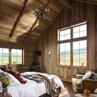 Ejemplo de dormitorio principal, rústico, con paredes marrones y estufa de leña
