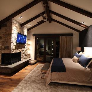 Esempio di una grande camera matrimoniale minimal con pareti nere, pavimento in legno massello medio, camino ad angolo e cornice del camino in pietra