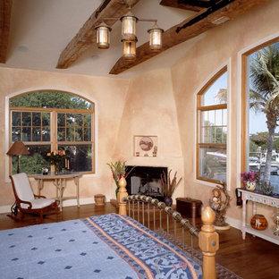 Aménagement d'une chambre parentale méditerranéenne de taille moyenne avec un mur beige, un sol en bois brun, un poêle à bois, un manteau de cheminée en plâtre et un sol marron.