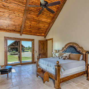 Design ideas for a large country master bedroom in Dallas with beige walls, travertine floors, a wood stove, a stone fireplace surround and beige floor.
