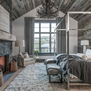 Modelo de dormitorio principal, rústico, con paredes grises, suelo de madera clara, chimenea tradicional, marco de chimenea de piedra y suelo beige