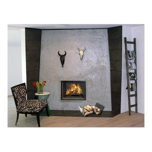 Foto de dormitorio principal, minimalista, pequeño, con suelo de madera clara, chimenea de esquina y marco de chimenea de hormigón