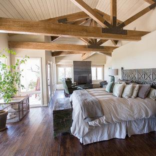 Foto di una grande camera matrimoniale stile rurale con pareti beige, parquet scuro, camino classico, cornice del camino in metallo e pavimento marrone