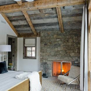 Immagine di una camera da letto rustica con pareti bianche, camino classico e cornice del camino in pietra