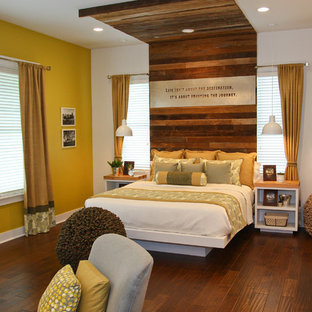 Country bedroom in Other with yellow walls and dark hardwood floors.